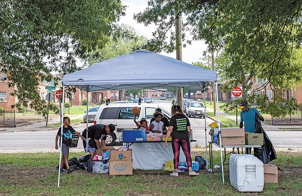 """Other volunteers staff a tent and welcome visitors to pick up supplies, including free books. The 381 Movement, a group that grew from protests following the police killing of George Floyd in Minneapolis in late May, is named for the successful 381-day Montgomery, Ala., bus boycott in 1955-56 against racially segregated seating that propelled Rosa Parks and Dr. Martin Luther King Jr. to national attention. The modern movement's goal is to offer solutions to racial and social injustice based on research, learning, legislation and volunteer initiatives that """"empower, educate and evolve the community."""""""