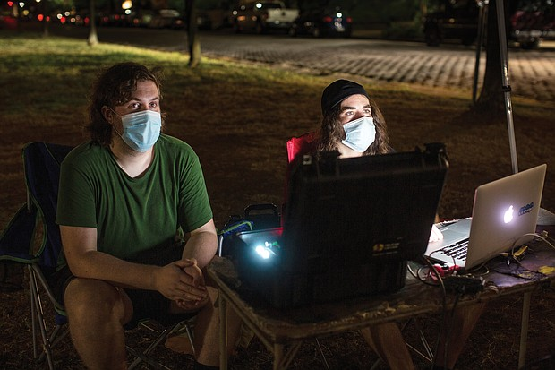 Alex Criqui, left, and Dustin Klein bring their understanding of history and technology to their nightly projections of images of African-Americans onto the Lee statue at Monument Avenue.