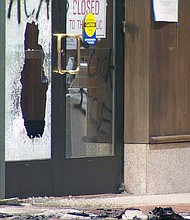 A Portland police officer stands guard outside the Multnomah County Building in southeast Portland late Tuesday night after police declared a gathering there a riot. It followed an attack on the building where a fire was started and windows broken. (KATU photo)