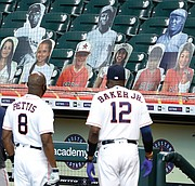 Houston Astros third base coach Gary Pettis and manager Dusty Baker Jr. look into the stands at photo cutouts of former Negro League players during a celebration of the 100th anniversary of the Negro Leagues before a game against the Seattle Mariners on Aug. 16 at Minute Maid Park.