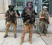 Armed members from private militia groups advocate for gun rights at Ninth and Main streets near the State Capitol before marching to the Siegel Center on Broad Street, where the House of Delegates was meeting tuesday in a special session. Several organizations held rallies on the opening day of the special General Assembly session, where lawmakers are taking up criminal justice, police reform and budget measures.