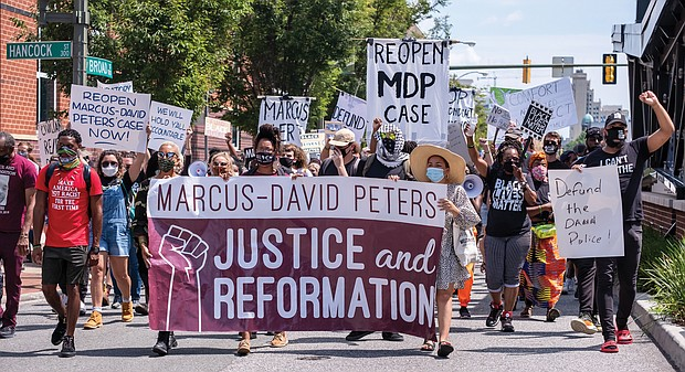 Marchers call for reopening the investigation into the 2018 fatal police shooting of Marcus-David Peters in Richmond during its march along Broad Street toward the legislative session at the Siegel Center. the state Senate is meeting at the Science Museum of Virginia.