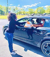Sherise handing out diapers during a She Rises Diaper Distribution event