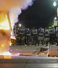 Police stand near a garbage truck ablaze during protests, Monday, Aug. 24 in Kenosha, Wis., sparked by the shooting of Jacob Blake by a Kenosha Police officer a day earlier.  (AP photo)