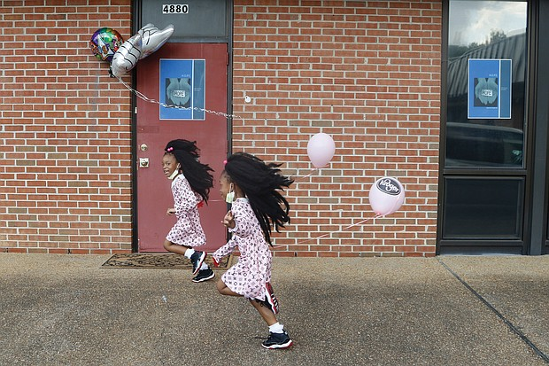 Wisdom Sadiq, 6, left, and her sister, shy Queen Sadiq, 5, have some fun following a program Aug. 8 blessing a new building now used by the H.O.P.E. Organization at 4880 Finlay St. in Henrico County. the girls, a double ball of energy, are relatives of the nonprofit's founder, Ollie Harvey. the organization assists people with food and other needs.