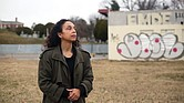 Lenora C. McQueen stands in the forgotten Grave Yard for Free People of Colour and For Slaves during a visit to Richmond. Behind her is the vacant, graffiti-marked mechanic's shop at 1305 N. 5th St. In the background is the Hebrew Cemetery.