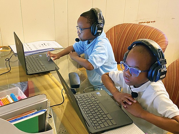 Chimborazo Elementary School students Kyle, 6, left, and Kevin Wilson, 8, connect with their teachers and classmates Tuesday, the first day of school, using Chromebooks provided by Richmond Public Schools. The kitchen table at the Wilson family's Fulton home was turned into a virtual classroom when school began at 9:15 a.m., with mom Safiya Wilson monitoring activity.
