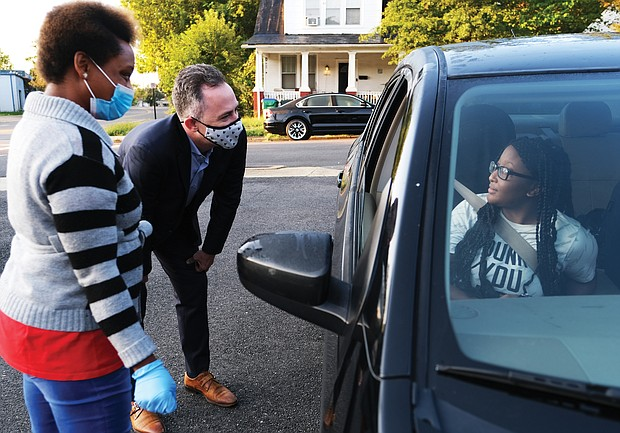 Richmond Public Schools nutritional worker Yukuri Canesius, left, and Superintendent Jason Kamras welcome Thomas Jefferson High school student Syasia Anderson and her family Tuesday morning at the meal distribution site in the parking lot of Ms. Girlee's Kitchen in Fulton before the start of virtual classes at 9:15 a.m.