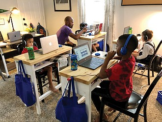 Pod leader Adam Evans works with Sebastian Wisnoski during online instruction with his Richmond Public Schools class at an education pod set up in the Evans family's North Side home. Other youngsters in the pod are, from left, Ace Evans, Blaize Evans and Bastian Van-Zandt.