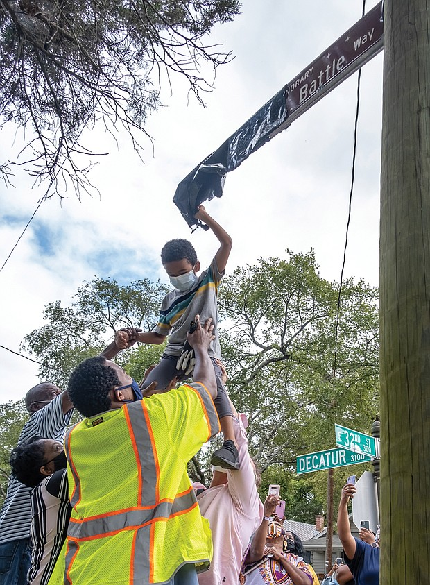 6-year-old Darren Fields, gets a lift from family and friends to unveil the street sign honoring his great-grandfather, the late Johnny R. Battle, at 32nd and Decatur streets in South Side. Mr. Battle mentored area youths and was a model neighbor. Ms. Trammell lobbied for the sign to help ease the hurt and sense of loss for those who knew Mr. Battle, 80, who was beaten in his wheel- chair and killed during an attack in April 2018 outside his home.