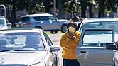 Gayle Clarke, a member of Moore Street Missionary Baptist Church, gets out of her car to listen to the sermon delivered by church pastor Dr. Alonza L. Lawrence during the church's drive-in homecoming service last Sunday in the parking lot of Hovey Field at Virginia Union University.