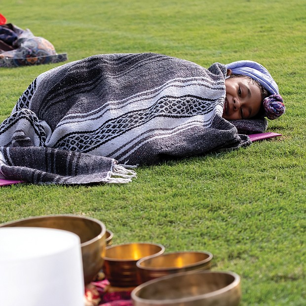Treasure Daily, 10, bundles up in the chilly outfield of The Diamond last Saturday and listens as her mother, Shanna Latia, conducts a sound therapy session during Project Yoga Richmond's Saturday Salutations. The nonprofit sponsoring organization is dedicated to making yoga accessible and affordable to Richmonders. The next Saturday Salutations session is scheduled for 9 to 10 a.m. Saturday, Oct. 17, at The Diamond on Arthur Ashe Boulevard.