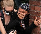 A crying woman is comforted during demonstrations in Louisville, Ky., where protesters clashed with police following Wednesday's announcement of the grand jury's decision in the criminal case against police officers involved in the March fatal shooting of Breonna Taylor.