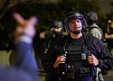 A protestor reacts towards a Portland police officer during protests, downtown, Saturday, Sept. 26. Protests which began since the police killing of George Floyd in late May have often resulted in late night clashes between protesters and law enforcement.  (AP photo)