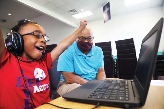 Kayden Bass, 6, a first-grader at Fairfield Court Elementary School, cheers himself on for the answer he gave during his virtual class Tuesday. He is part of the Project Stay Connected/Stay on Point learning pod, where volunteer Arthur Gregory, a retired DuPont employee, works with students.
