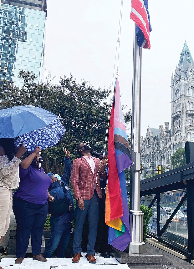 """Mayor Levar M. Stoney prepares to raise the Progress Pride flag outside City Hall's Broad Street entrance. It is the first time a symbol of the gay community has flown outside the 18-story municipal center in Downtown. The multicolored flag went up last Friday in recognition of Richmond's annual PrideFest weekend and flew through Wednesday when Virginia PrideFest Month ended. The mayor stated the flag was raised to let LGBTQ Richmonders """"know that this city stands behind them.""""  The Progress Pride flag was chosen because, along with traditional rainbow colors, it incorporates additional stripes to symbolize the inclusion of African-Americans, Latinos, people of color, transgender individuals and those living with HIV/AIDS. Lacette Cross and Louise """"Cheezi"""" Farmer, founders of Black Pride RVA, were among the participants at the upbeat ceremony. Black Pride RVA also received Virginia Pride's annual Firework Award for being catalysts for community change."""