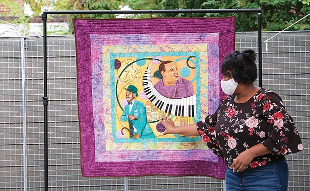 Richmond quilt artist Unicia Buster, who was commissioned to create the official poster for this year's 2nd Street Festival, displays her creation that was photographed for the festival poster. Venture Richmond unveiled the official work at an event Sept. 23 at the Visual Arts Center's Cabell Courtyard.