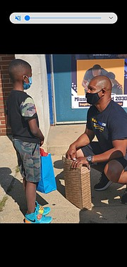 Gerald Moore Sr., right, speaks to a student about scholastic achievement, after giving a Chromebook and gifts to him.