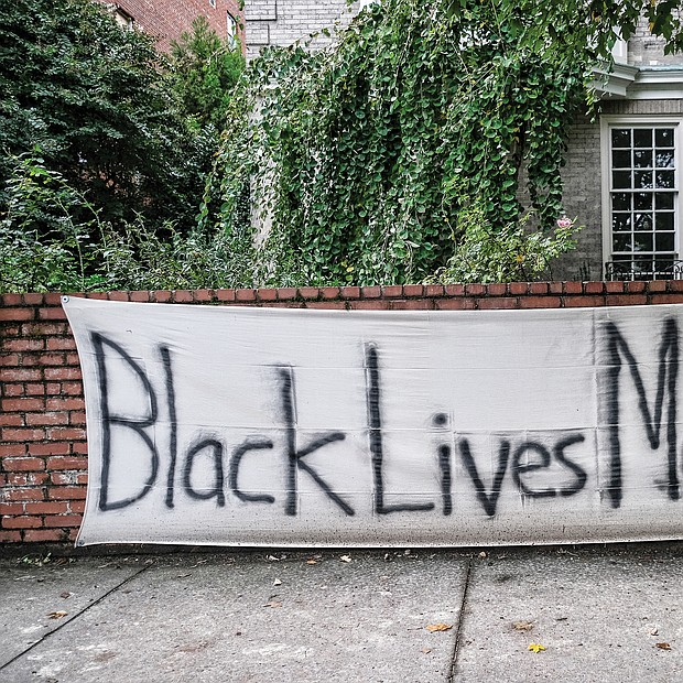 "A sign of support or a statement? This homemade ""Black Lives Matter"" banner was spotted on a brick wall in front of a Monument Avenue residence near Allen Avenue, the intersection where the huge statue to Confederate Gen. Robert E. Lee stands on a traffic circle. The area around the statue has been the epicenter of protests over racial injustice and police brutality since May. Signs like this one and logos with BLM have become commonplace on businesses and other buildings in and near Downtown and the circle following an early spate of window-smashing, fires and looting. The signs often were posted as plea for anyone bent on destruction to spare a structure."