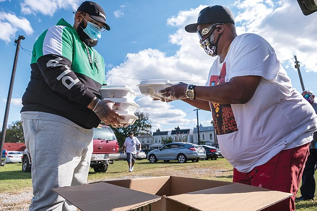 Corey Tolliver and Kevin Evans help distribute dinners to the dozens of people who attended the event.