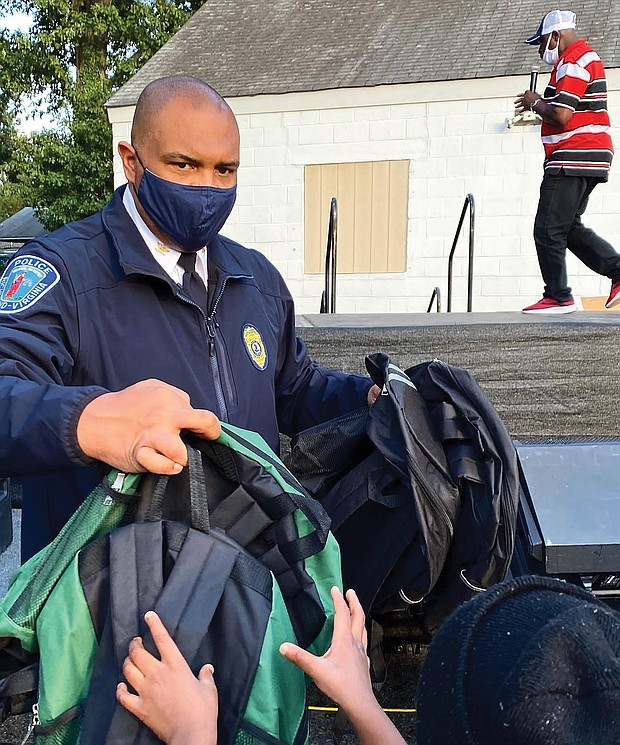 Chief Smith hands out backpacks to youngsters at National Night Out.