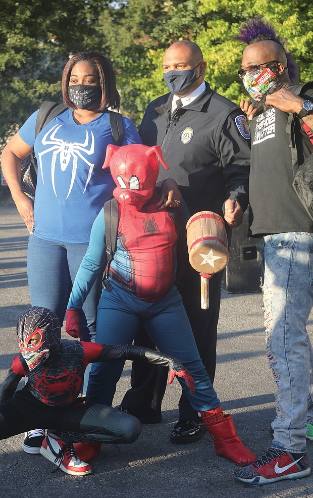 """Chief Smith joins a family for a photo. Daryle Williams-Lester, left, Frank Lester, and their two sons, """"Spider-Ham"""" Darick Williams, 11, and """"Spiderman"""" Darian Williams, 9."""