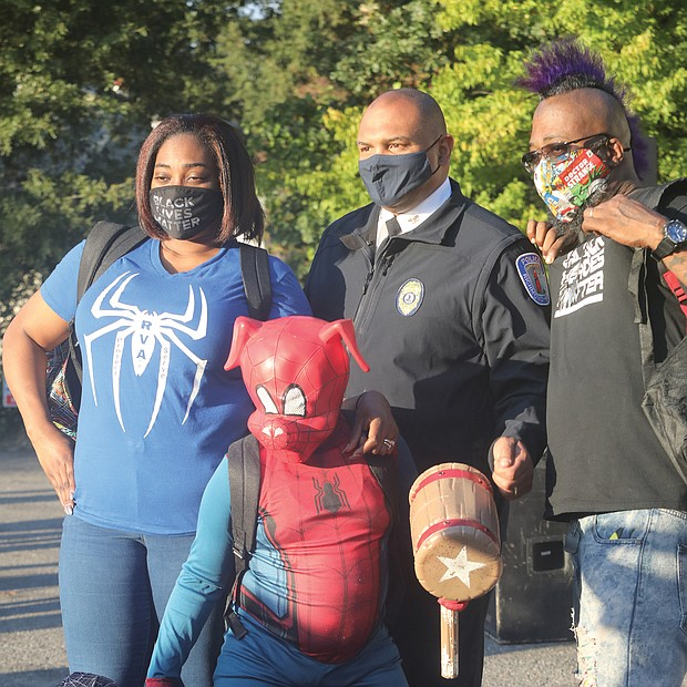 "Chief Smith joins a family for a photo. Daryle Williams-Lester, left, Frank Lester, and their two sons, ""Spider-Ham"" Darick Williams, 11, and ""Spiderman"" Darian Williams, 9."