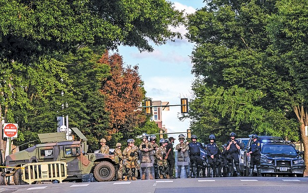 Richmond Police officers stand with National Guard members and Virginia State Police troopers at Madison and Grace near Police Headquarters in June in Downtown Richmond.