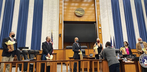 """Mayor Levar M. Stoney, front center, talks with special guests at a ceremony Oct. 9 in Richmond City Council Chambers proclaiming Monday, Oct. 12, as Indigenous Peoples' Day in the city. This is the second year the city has honored the day, which was formerly dedicated to Christopher Columbus, who many view as exploiting indigenous people. In June, a statue of Columbus was pulled down from its perch in Byrd Park by protesters and dragged into Fountain Lake. The city now has the statue in storage. Guests at the ceremony are, from left, Keith Anderson of Portsmouth and Chief Samuel Bass of Suffolk, both of the Nansemond Indian Nation; Reggie Tupponce Jr. of Glen Allen, administrator of the Upper Mattaponi Indian Tribe; Shereen Waterlily of Richmond, a representative of the Mattaponi Tribe; Dr. Denise L. Walters of Henrico, a member of the Nottoway Tribe Council; and Pamunkey Chief Robert Gray of King William County. Monday also was proclaimed Indigenous Peoples' Day in Virginia for the first time. In a statement, Gov. Northam said the state and the nation """"too often failed to live up to our commitments with those who were the first stewards of the lands we now call Virginia — and they have suffered historic injustices as a result. """"Indigenous Peoples' Day celebrates the resilience of our tribal communities and promotes reconciliation, healing, and continued friendship with Virginia's Indian tribes,"""" the statement continued. """"In making this proclamation, we pay tribute to the culture, history, and many contributions of Virginia Indians and recommit to cultivating strong government-to-government partnerships that are grounded in mutual trust and respect."""" Virginia is home to 11 state-recognized Indian tribes, seven of which also are federally recognized."""