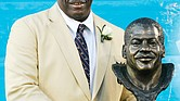 Former San Diego Chargers defensive end Fred Dean stands next to his bronze bust at his Pro Football Hall of Fame induction in 2008 in Canton, Ohio.