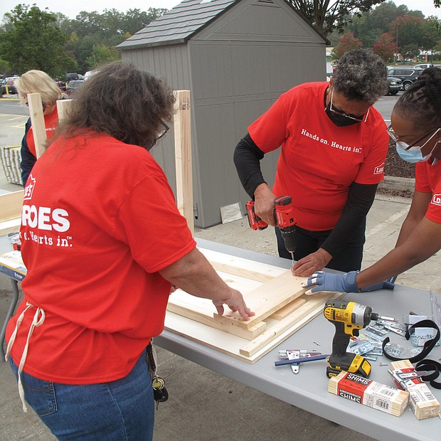 Richmond City Councilwoman Ellen F. Robertson, center, assembles a desk with the help of Anita Sawyer, left, and Fatemia Gunter, two employees of Lowe's home improvement store. Employees at the Sheila Lane store in South Side volunteered to put together 500 fold-up desks for Richmond Public Schools students who are learning at home during the pandemic. About 25 Lowe's employees started the project last week, with 100 desks being produced each Tuesday. The desks will be given to students free of charge.