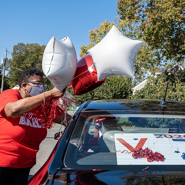 Chandra Hurst, president of the chapter, ties down balloons for the spirited, civic-minded caravan. The sorority chapter is hosting a similar event Saturday, Oct. 31, to rally voters in New Kent and Charles City counties.