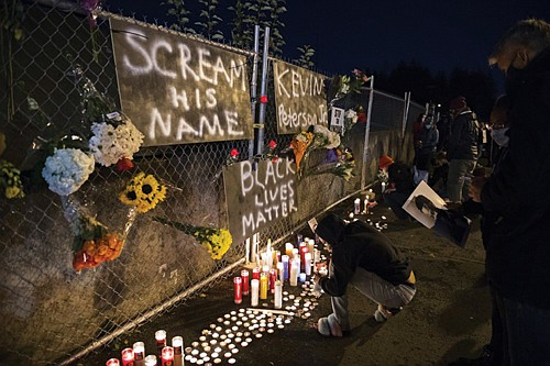 Mourners pause to remember Kevin Peterson Jr., a 21-year-old Black man who was fatally shot Thursday in the Hazel Dell community of Vancouver by Clark County law enforcement. The candlelight vigil was held Friday night outside of the Hazel Dell branch of U.S. Bank where the shooting took place.  (AP photo)