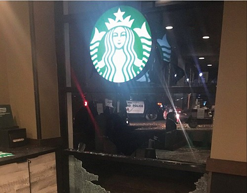 A shattered window at the Starbucks on Southwest Montgomery Street near Portland State University was one of several targets of protesters Monday. Windows were also broken at the PSU Public Safety Office and other university buildings.