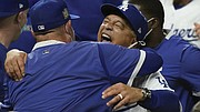 Winning manager Dave Roberts, left, hugs pitcher Julio Urias.