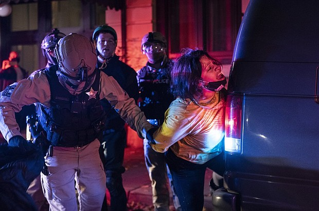 Police arrest a protester in Portland Wednesday night on an evening when clashes and vandalism broke out during marches for justice and demands for the counting of votes in the presidential election, one day after the Nov. 4 vote. (AP photo)