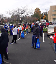 """Community members, most of whom were senior citizens, wait in line to receive hot meals at the """"All Walks of Faith Summit"""" at Baltimore City Community College on Oct. 24, 2020."""