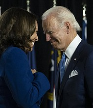 Democratic presidential candidate former Vice President Joe Biden and his running mate Sen. Kamala Harris, D-Calif., pass each other as Harris moves to the podium to speak during a campaign event Aug. 12 in Wilmington, Del.  (AP photo)