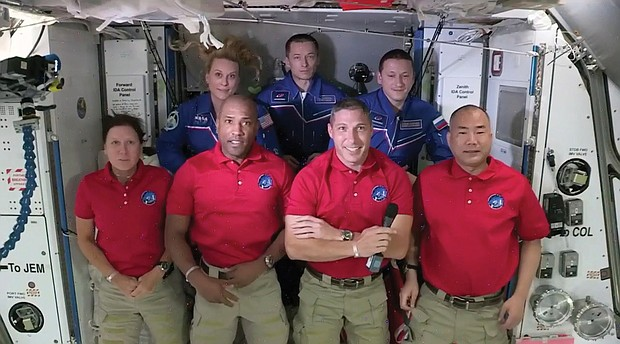 In this frame grab from NASA TV, the SpaceX Dragon crew, from front left to right, Shannon Walker, Victor Glover, Mike Hopkins and Soichi Noguchi stand with the International Space Station crew, Kate Rubins, back row from left, Expedition 64 commander Sergey Ryzhikov and Sergey Kud-Sverchkov during a welcome ceremony, early Tuesday. The Dragon arrived and docked at the ISS late Monday.