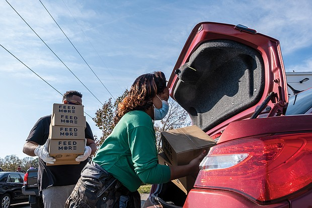 Volunteers Whitney Edmonds and Taikein Cooper help load food donated by FeedMore into a waiting car.