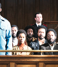 "Malachi Kirby as Darcus Howe (left, light blue jacket), Letitia Wright as Altheia Jones-LeCointe (center left, orange top), Shaun Parkes as Frank Crichlow (center right, black jacket), Rochenda Sandall as Barbara Beese (right, black sweater), Richie Campbell as Rothwell Kentish, Gershwyn Eustache, Jr. as Eddie LeCointe (second row center), Nathaniel Martello White as Rhodan Gordon in ""Mangrove."""