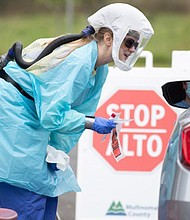 A health care worker wears protective clothing to test people at a COVID-19 testing site east of Portland.  (Photo courtesy of Multnomah County)