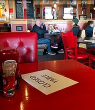 Restaurants, food carts and benevolent groups in Multnomah County can apply for small business grants to offset the cost of restrictions from COVID-19. A photo from AP earlier in the year shows seating restrictions to control the disease taken at a Tigard Red Robin restaurant.