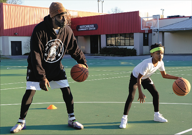 Chrishona Wilson, 8, works on her basketball skills with Coach Jonathan Hargett at Hotchkiss Field Community Center in North Side last Saturday. The youngster, who attended practice with her stepmother, played last year for the South Side Ducks, a youth team under the auspices of the city Department of Parks, Recreation and Community Facilities.