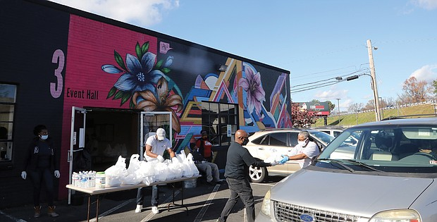 """Thanksgiving 2020 was a different sort of holiday, with community events geared toward carry-out meals rather than a communal, sit-down dinner because of the pandemic. Above, at Diversity Richmond in North Side, volunteer Perone Johnson, left, hands a packaged hot Thanksgiving dinner to Luise """"Cheezi"""" Farmer, Diversity Richmond's board chair, who in turn will hand it to motorists in drive-thru set up in the parking lot. BlackPrideRVA partnered with Diversity Richmond and Ms. Girlee's Kitchen to provide 200 hot meals on Thanksgiving to all who wanted them. Last year's inaugural event was a family-style dinner for 150 people."""