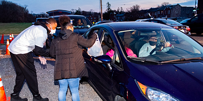 Members of the community drive up to receive Thanksgiving meals outside of Hilton Recreation Center on November 24, 2020.