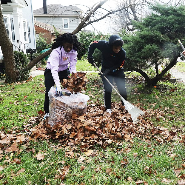 Cousins Armari Fells, 14, left, and Jeremiah Jefferson, 16, pitched in to help their grandfather, Tyrone Prentiss, spruce up the yard of his sister and her husband, Patrick and Delores Llewellyn, on brook Road in North Side. They took advantage of the sunshine last Saturday to rake and bag the leaves for pickup. Armari, who lives in Atlanta where his schooling is now virtual, has been visiting relatives in Richmond since Thanksgiving.
