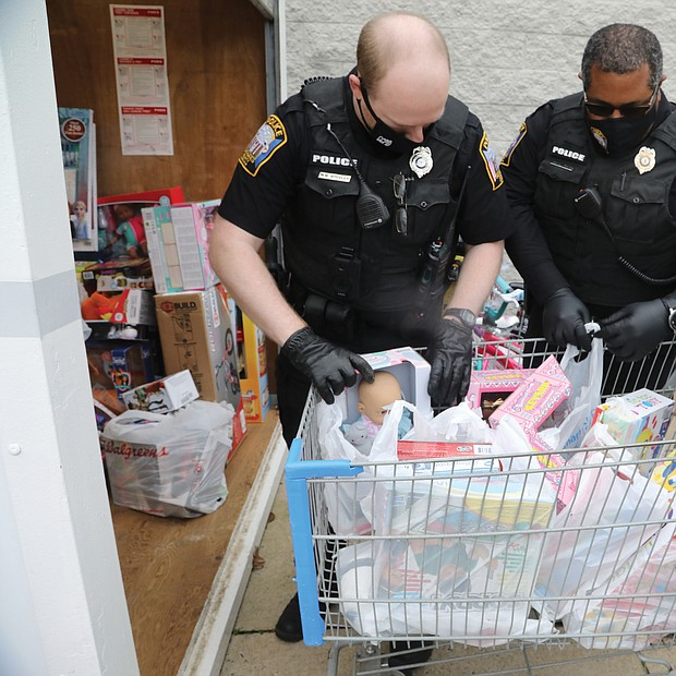 Officer Matt Wheeler, left, and Sgt. George Turner of the Chesterfield Police Department load donated toys into a storage container until they can be distributed.