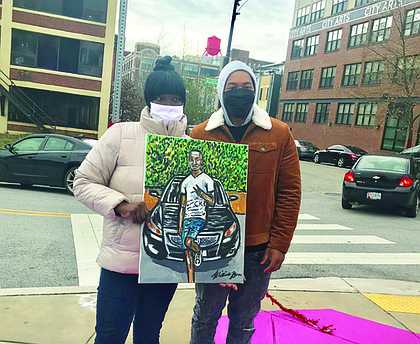 Tynette Robinson holds a portrait of her son Devonte Robinson who was killed in 2019. She is pictured with artist Will Brown.