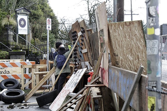 A perimeter of street and sidewalk barricades erected by protesters to oppose the eviction of a long time Black and ...